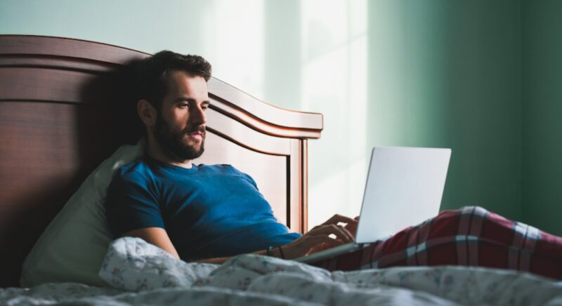 Student arbeitet im Bett an seinem Laptop