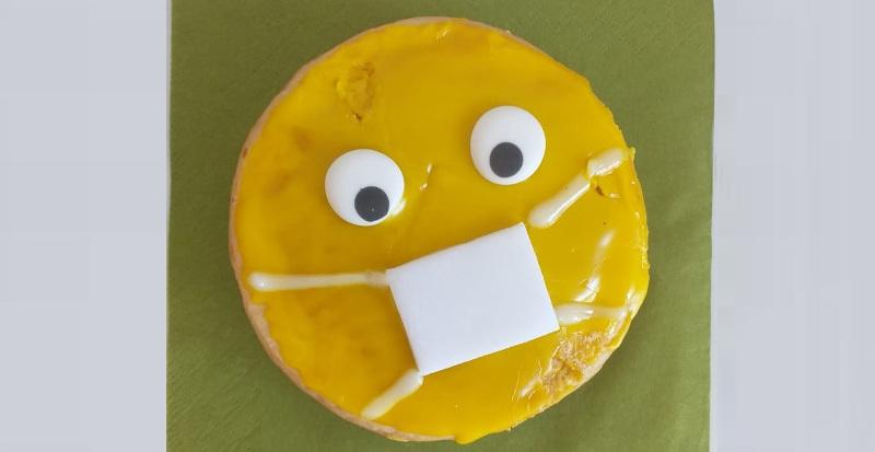 Foto eines selbstgebackenen Amerikaners mit Zuckerglasur. Das Gesicht trägt einen Mundschutz.